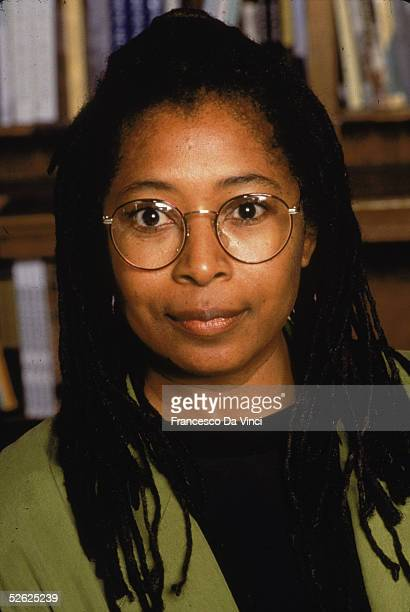 Headshot portrait of American author Alice Walker as she poses in front of a bookcase 1991
