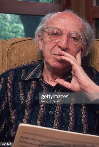 Headshot portrait of American composer Aaron Copland sitting and holding a musical score with his hand up to his face