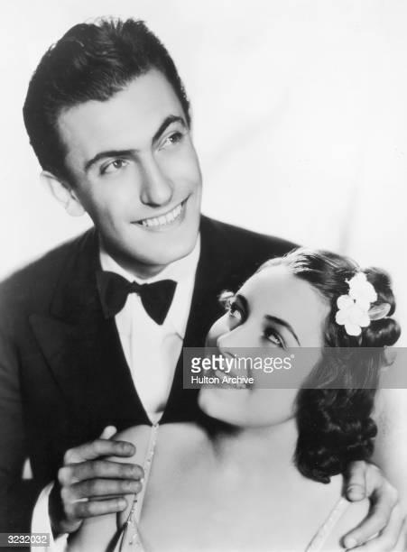 Headshot portrait of American jazz pianist and bandleader Eddy Duchin smiling behind singer Durelle Alexander as he places his hands on her shoulders...