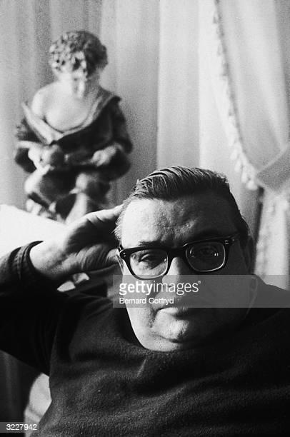 Headshot portrait of American writer Mario Puzo author of the novel The Godfather sitting on a sofa
