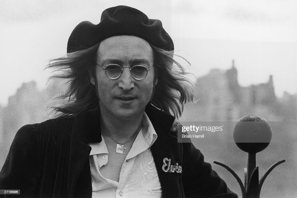 Headshot portrait of British rock singer and songwriter John Lennon (1940-1980) standing on the roof of his apartment building, the Dakota, New York City. He wears a wool beret and an 'Elvis' pin on his jacket.
