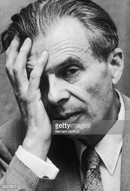 Headshot portrait of British writer Aldous Huxley holding his hand to his face New York City