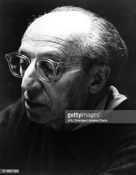 Headshot portrait of composer and writer Aaron Copland with thick clear glasses with a serious facial expression looking downwards faced to his right...