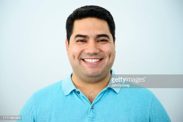 ritratto a colpo di testa di uomo ispanico maturo sorridente - maglietta polo foto e immagini stock