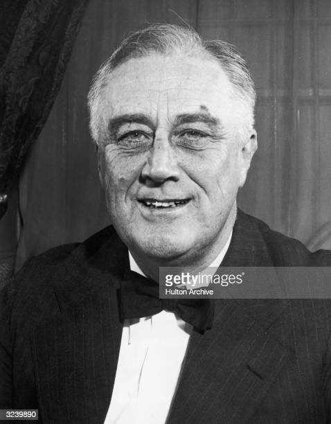 Headshot portrait of US president Franklin D Roosevelt smiling while wearing a coat and bow tie