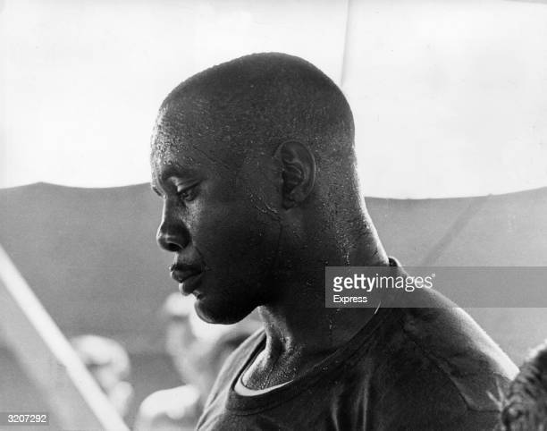 Headshot profile of American Heavyweight Champion boxer Sonny Liston sweating from practice at his training camp in South Fallsburg New York