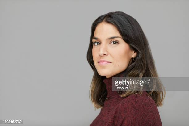 headshot studio portrait of a woman in profile looking at the camera. - side view stock pictures, royalty-free photos & images