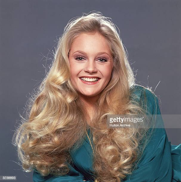 Headshot studio portrait of American actor Charlene Tilton wearing a blue shirt and smiling