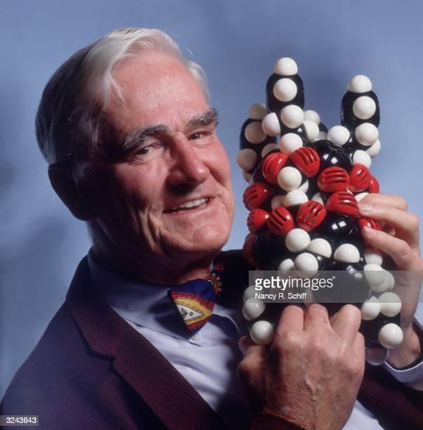 Headshot studio portrait of Nobel Prizewinning American chemist Dr Donald Cram holding a DNA molecular model close to his face