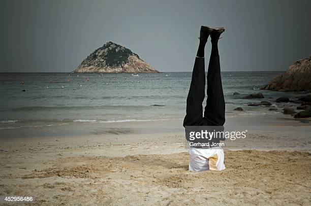 A headstand yoga pose on the beach MODEL RELEASED