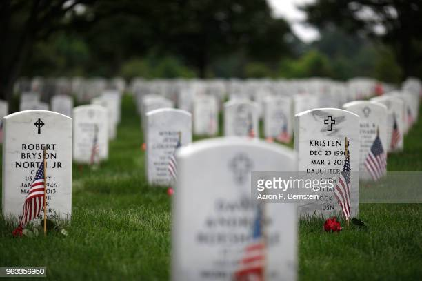 Headstones are adorned with flags at Arlington National Cemetery on Memorial Day May 27 2018 in Arlington Virginia Mourners from throughout the...