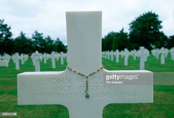 Headstones at a United States Military Cemetery at Utah Beach in Normandy France Flowers have been left beside one of the crosses