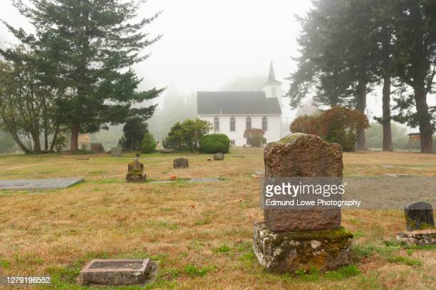headstones in a small cemetery behind a white wooden church. -  キリスト教 伝来の地  ストックフォトと画像