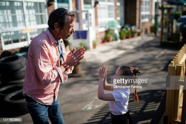 Headteacher Bob Merrell and a young girl greet each other as children of key workers take part in school activities at Oldfield Brow Primary School...