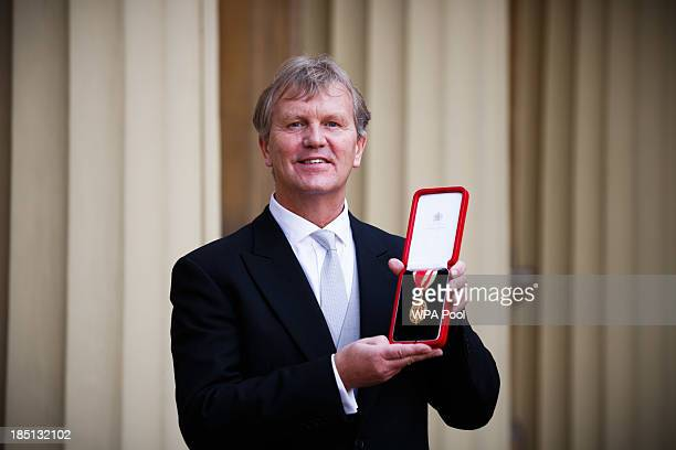 Headteacher Sir Kenneth Gibson poses after receiving his Knighthood from Prince William Duke of Cambridge at an Investiture ceremony at Buckingham...