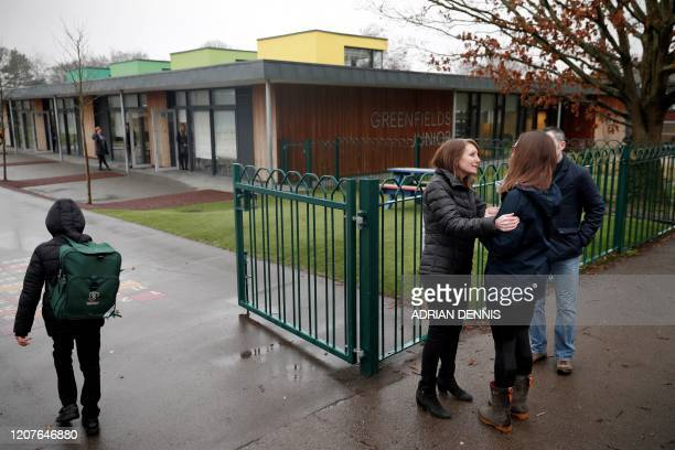 Headteacher Sue Tadman comforts a parent as she talks with them outside of Greenfields Junior School in Hartley Wintney west of London on March 19 as...