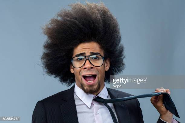 Headwind in business. cool businessman with big afro hair holding his necktie, looking surprised in the camera