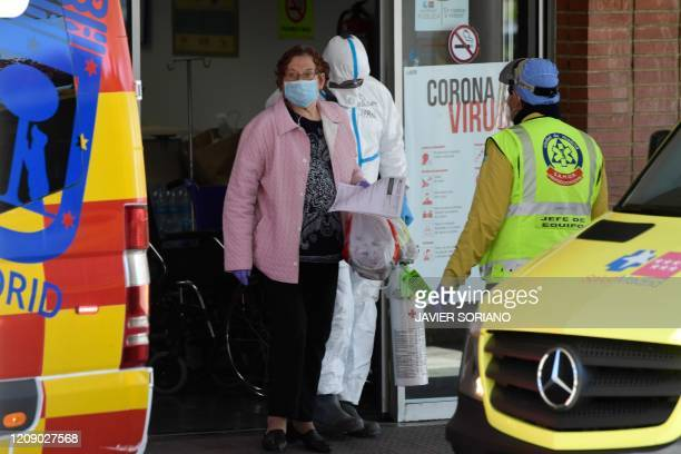 Healcare workers wearing protective suit help a patient at the Severo Ochoa Hospital in Leganes near Madrid on April 03 before her transfert to the...