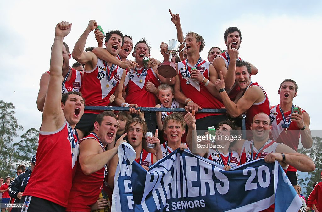 Healesville players celebrate after being presented with the premiership flag and trophy after winning the Yarra Valley Mountain District Football League Division 2 Seniors Grand Final between Healesville and Seville at Yarra Junction Football Ground on September 14, 2013 in Melbourne, Australia.