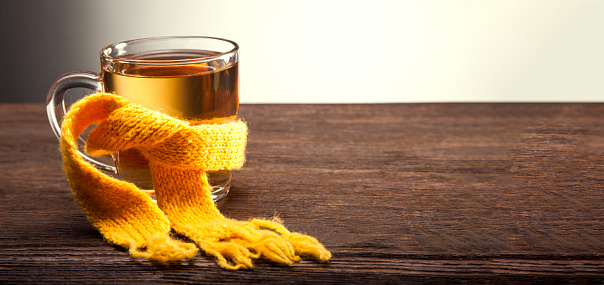 Healing glass of tea in a scarf on a wooden background 1023398488