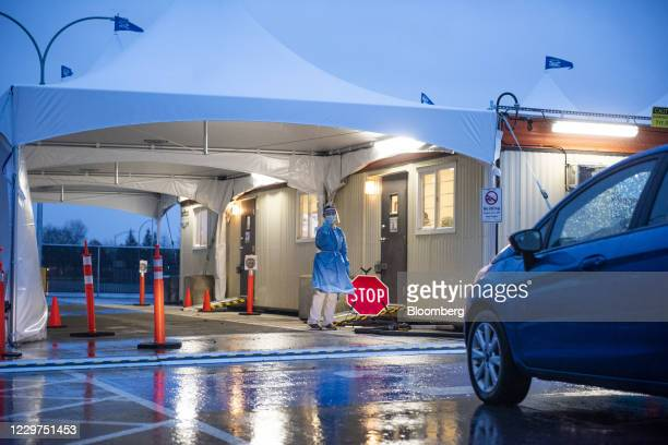 Healtcare worker gestures for a vehicle to enter a new Covid-19 test collection center near the Vancouver International Airport in Richmond, British...