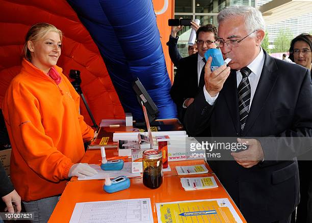 EU Health and Consumer Policy commissioner John Dalli uses a breathalyzer during the World No Tobacco Day at the EU headquarters in Brussels on May...