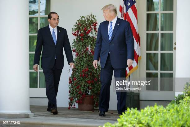 S Health and Human Services Secretary Alex Azar and President Donald Trump walks into the Rose Garden before making an announcement about drug prices...