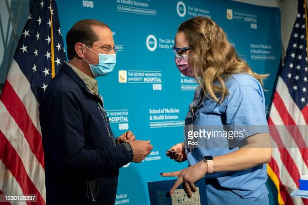 Health and Human Services Secretary Alex Azar smiles after handing a challenge coin to Shylee Stewart, a labor and delivery nurse, after she received...