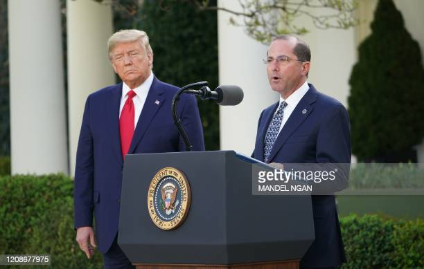 Health and Human Services Secretary Alex Azar speaks as US President Donald Trump listens during a Coronavirus Task Force press briefing in the Rose...