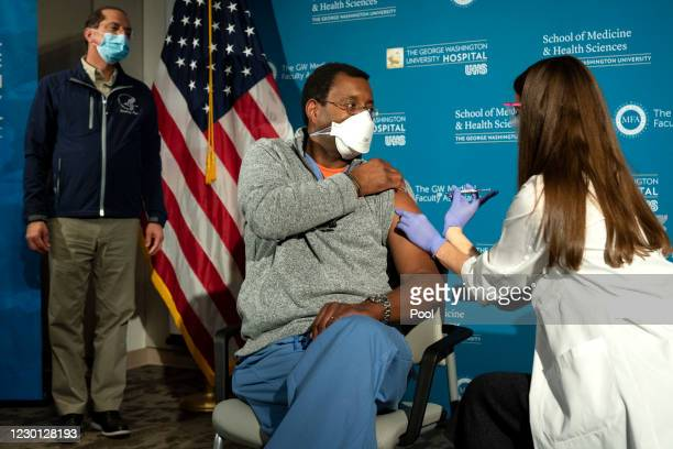 Health and Human Services Secretary Alex Azar watches as Dr. Raymond Pla, an anesthesiologist at George Washington University Hospital, is vaccinated...