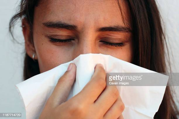 health and medicine concept - young woman blowing nose into tissue. - mucus stock pictures, royalty-free photos & images