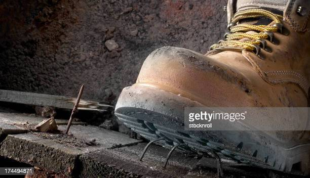 Health and safety Dirty work boots stepping on a nail