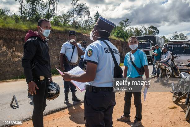 Health authorities and police forces stop pedestrians and southbound vehicles some 20km south of Antananarivo to check their temperature and the...
