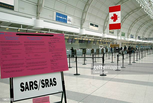 Health Canada Notice about Severe Acute Respiratory Syndrome stands in Terminal 3 at Toronto's Pearson International Airport April 30 2003 With more...