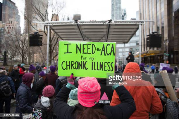 A health care activist lifts signage promoting the Affordable Care Act during a rally as part of the national 'March for Health' movement in front of...