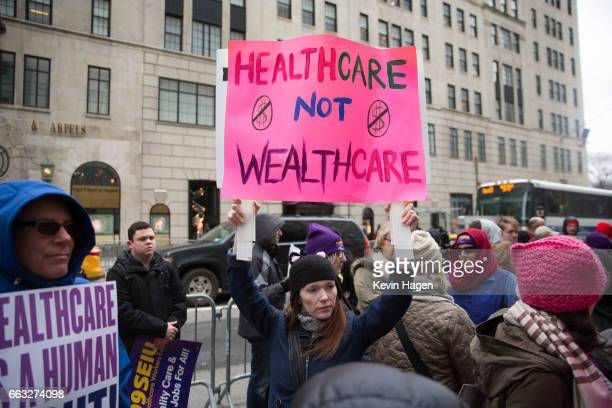 Health care activists lift signage promoting the Affordable Care Act during a rally as part of the national 'March for Health' movement in front of...