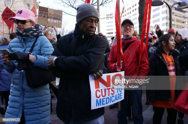 Health care activists protest infront of the Trump International Hotel on March 23 2017 in Washington DC / AFP PHOTO / MANDEL NGAN
