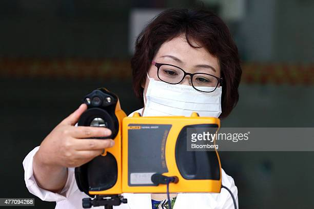 A health care center employee inspects a thermographic camera at a subway station in Bucheon South Korea on Sunday June 14 2015 South Korea reported...