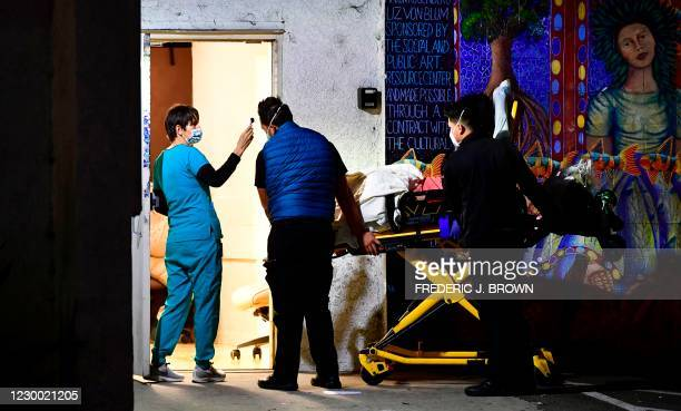 Health care professionals get temperature checks upon arrival at an urgent care facility in Los Angeles, California on December 8, 2020. - An...