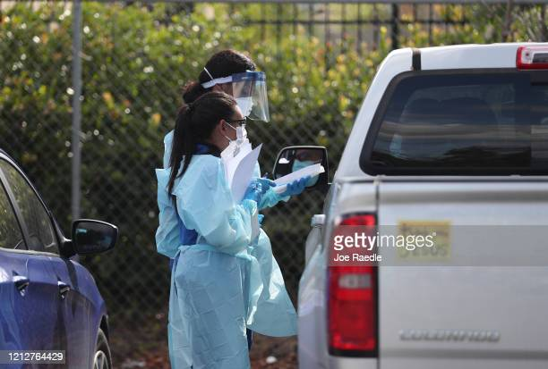 Health care staff from the FoundCare center wear protective gear as they help people who called to setup a drive through appointments to be tested...