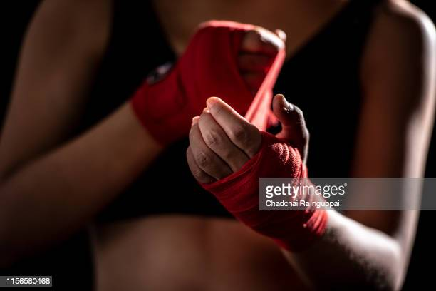 health care women are exercising by punching and are wrapped in red cloth at the hands before punching in the gym. - boxing stock pictures, royalty-free photos & images