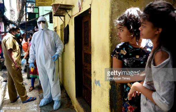Health care worker checks the temperature in the Dharavi slums during Covid-19 pandemic, on June 20, 2020 in Mumbai, India.