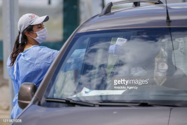 A health care worker controls temperatures of drivers and passengers in Antalya Turkey on May 05 2020 after the Turkish government lifted the...