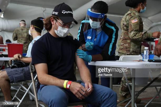 Health care worker immunizes JP Bejarano with the COVID-19 vaccine at the Miami Dade College North Campus on March 10, 2021 in North Miami, Florida....
