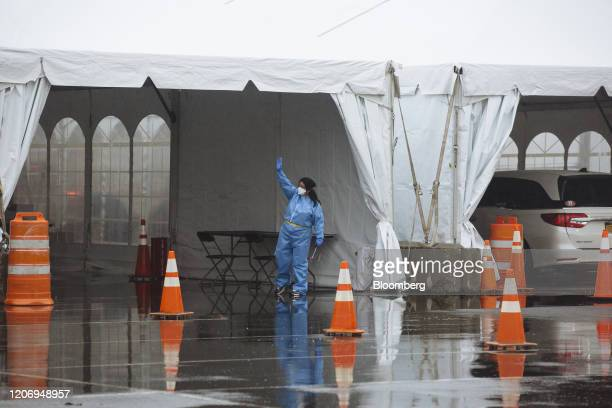 A health care worker in a protective suit gestures inside a six lane COVID19 drivethrough testing facility at Glen Island Park in New Rochelle New...