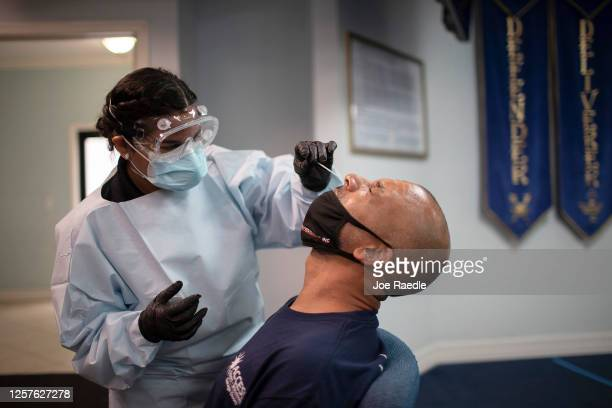 Health care worker use a nasal swab to test Eric Rodriguez for COVID-19 at a pop up testing site at the Koinonia Worship Center and Village on July...