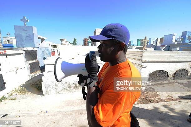 Health care worker uses a bull horn to remind visitors to wash their hands to prevent cholera as Haitians pay homage to relatives on All Saints' Day...