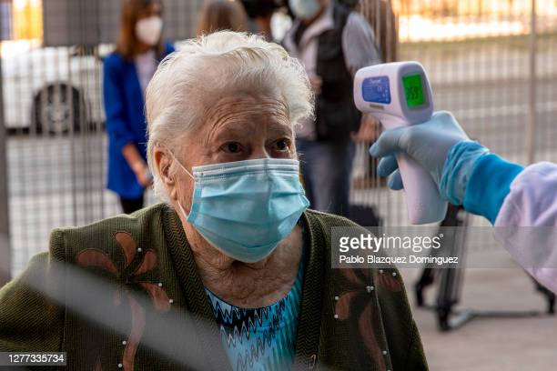 Health care worker uses a spot infrared thermometer to measure the body temperature of a woman before she has a rapid COVID-19 disease antigen test...