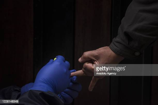 A health care worker wearing personal protective equipment takes a fingertip blood sample for diagnosis by IgG/IgM Rapid Tests during a large...