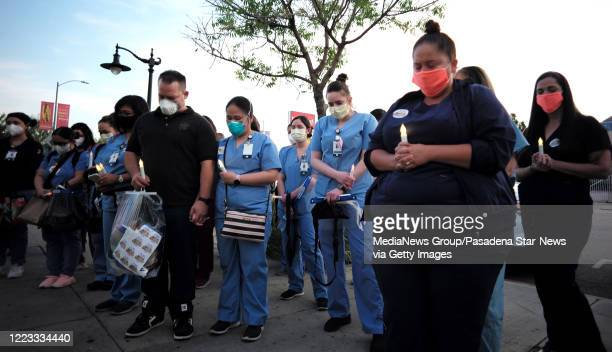 Health care workers bow their head as a prayer is said during a memorial and candle light vigil for Hollywood Presbyterian Nurse Celia Marcos who...